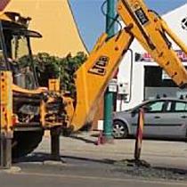 Un muncitor sparge cu excavatorul carosabilul de pe Martirilor